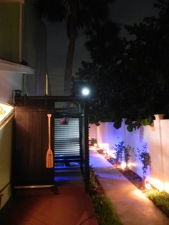 Night time view of side yard and outdoor shower.