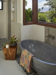 Decadent stone soaking tub with gorgeous natural light and full privacy.