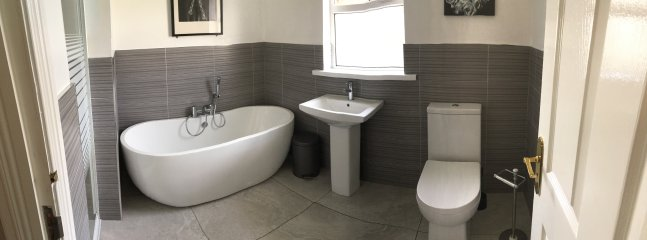 Newly installed modern bathroom suite with large shower cubicle.