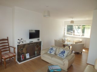 The large light, bright living area on the middle floor with flat screen TV and selection of seat.