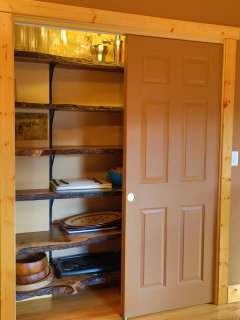 Live edge black walnut shelves in the oversize pantry are ready to welcome your groceries