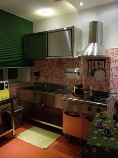 Cucina a norma Mareno  tutta in acciaio inserita in un contesto di calda accoglienza