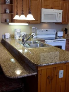 View of the kitchen showing appliances. there is also a bar counter top.