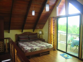 Upstairs bedroom with large queensized bed and 2 single beds.
