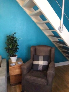 View of stairway and comfy rocking chair #2. Note the safe and secure banister and handrails.
