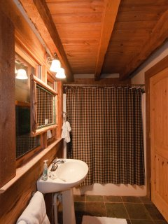 The two bathrooms are also charming with log mirrors and look out onto the mountain greenery with one window facing a...