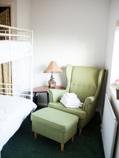 Third bedroom with bunk beds and loung chair overlooking the garden.