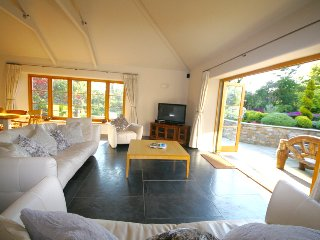 Lounge area with folding doors over looking out door alfresco dining, sun terrace and gardens