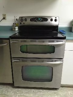 High-end kitchen range, glass top heating element with warming Center, dual oven.