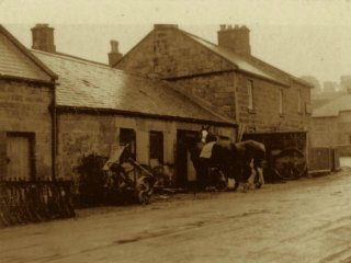 The local Blacksmiths. Back in the day. The cottage is in the square behind.
