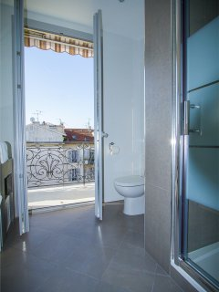 The second bathroom holds a walk-in shower, wash basin, mirror and toilet seat.