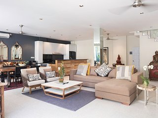 Luxuriously furnished, spacious living and dining area with an open-plan kitchen.