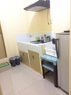 Kitchen with refrigerator, induction cooker and electric kettle.
