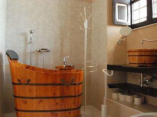 bagno con vasca e finestra sui tetti di Sutri della prima camera da letto matrimoniale