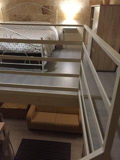 particolare della veduta del letto e della zona living in cui vi è posizionato il divano letto