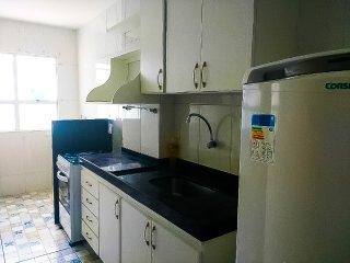 Cozinha com armários, fogão, geladeira e utensílios.