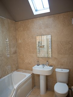 Old Dairy - Main Bathroom with over head shower and curved bath