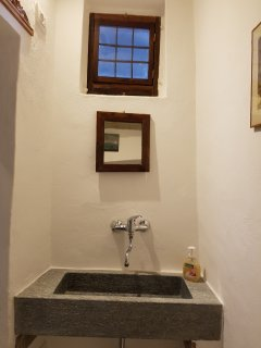 Antique stone washbasin in en-suite toilet including ventilation & small window.