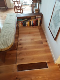 Wooden safety trapdoor that closes staircase opening. Guest library area.