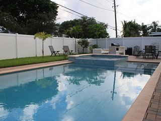 Pool, spa and patio with gas grill, table with chairs and lounge chairs.
