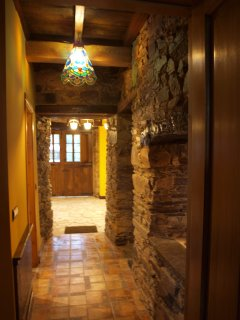 Pasillo que comunica salones, cocina, aseo y escaleras a planta de habitaciones.