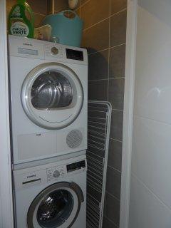 Laverie privée avec machine à laver et sèche linge.