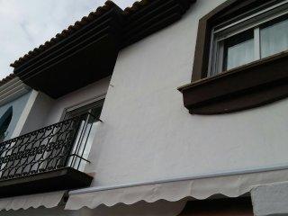 Fachada principal, primera planta con balcón y toldos en el patio delantero