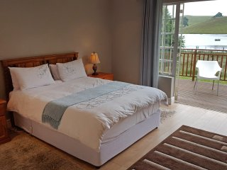 Main bedroom has ceiling fan and hairdryer. Doors lead out onto wooden deck overlooking the dam