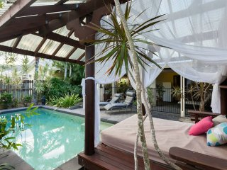 View across the pool and daybed to the large entertaining area and bbq