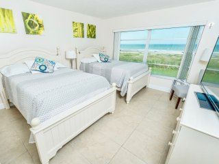 The first guest bedroom faces the ocean, has two double beds and a big screen TV.