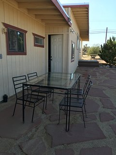 Outdoor patio with dining table and 4 chairs overlooking the 2 1/2 acre private landscape