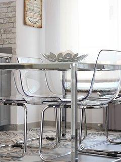 Detalle mesa de cocina y sillas, cristal y acero.