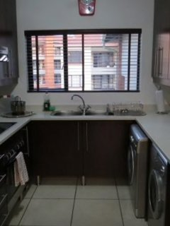 Light and airy kitchen area with refrigerator, washer, dryer, stove, oven.