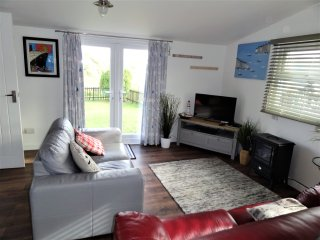 Comfortable, well furnished lounge with a view of the garden and dunes.