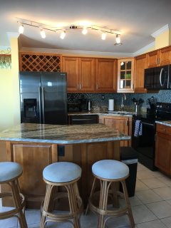 Updated kitchen with granite counters and new black stainless appliances.  Seating at island