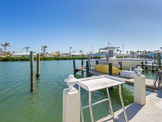 View of 200 foot waterway canal, large boat dock and cleaning fish table.  Dock has a water hose
