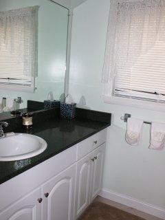 The en suite bath has a granite topped vanity and tile flooring.