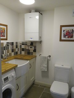 Utility room with washer dryer and downstairs toilet.
