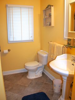 The nearby hall bathroom has a pedestal sink and shower/tub.