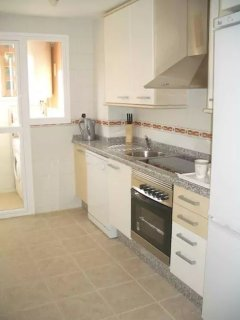 Kitchen with cooker, electric hob, microwave, dishwasher, washing machine, adult and kids cutlery an