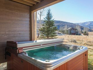 Rustic home w/ private hot tub; mountain views & fireplace