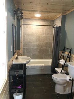 First floor full bathroom from bedroom entrance. Tile floors and shower walls.