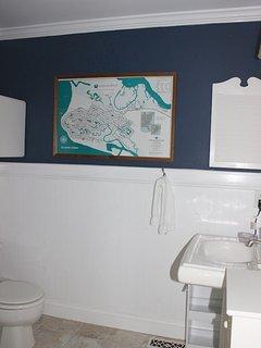 The master bath has wainscot, a pedestal sink and tile flooring.