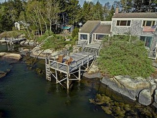 Aerial shot of cottage, deck, and water