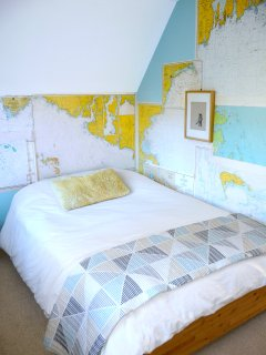 The guest room (full-sized bed) is decorated with vintage nautical maps.