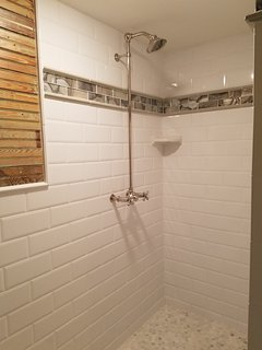 Deep tiles shower with corner seat, multiple hooks and dual water controls
