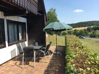 Offenes Grundstück mit Seeblick von Terrasse und Balkon Terrassenmöbel, Grill, Liegestühle.