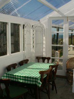 conservatory, with table and seating for breakfast with sea view