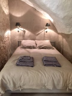 the bedroom area with natural linen bedding