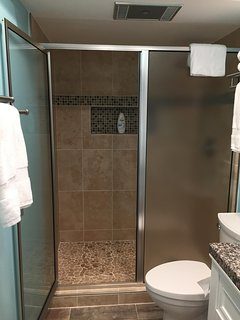 Newly renovated walk-in shower with stone floor.